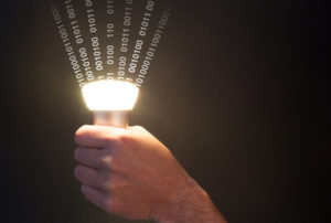 Hand holds a glowing bulb emitting data